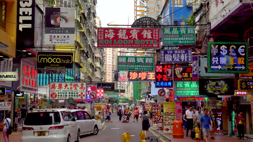 Hong Kong June 2016: Many traditional Chinese signs on busy street. Busy street with people and cars in Kowloon area. Densely packed traditional Chinese signs in commercial downtown area in China.