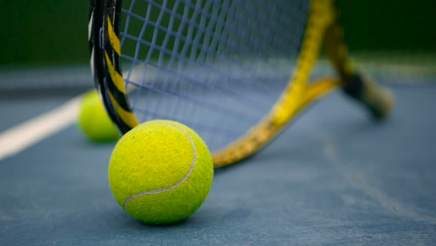 Close up of tennis equipment on the court. Sport, recreation concept. Yellow racket with a tennis ball in motion on a clay green blue court next to the white line with copy space and soft focus. #1014431090
