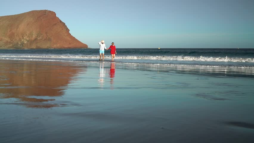 Couple in love carefree walking from the water on the beach. Picturesque ocean coast of Tenerife, Canarian Islands, Spain