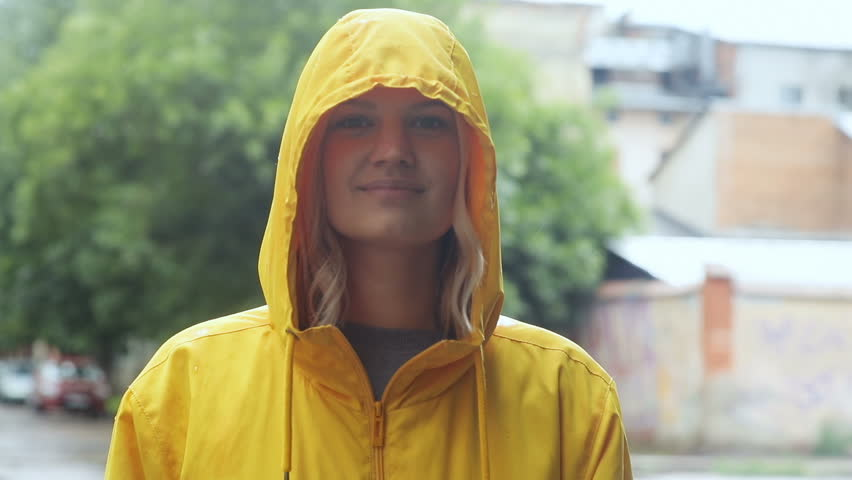 outdoors portrait of beautiful happy young woman wearing stylish yellow raincoat hoodie jacket with a hood smiling and looking at camera having fun cheerful joyful girl showing tongue laughing joke