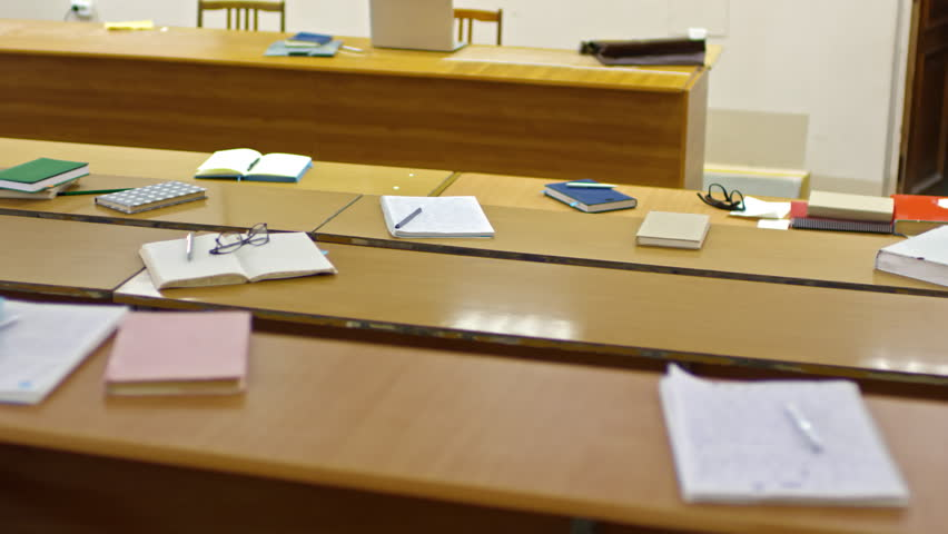 Tracking shot of empty lecture theater at university with notebooks and school supplies left on desks #1014467900