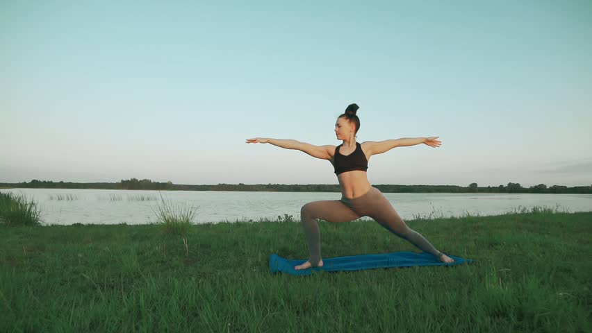 Young woman wearing doing yoga in morning at lake on blue yoga mat in quiet scenery. Woman doing yoga. Healthy lifestyle concept in slow motion with copyspace