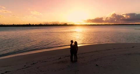 a couple on the beach with sunset