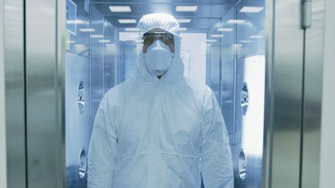 Scientist / Virologist / Factory Worker in Coverall Suit Disinfects Himself in Decontamination Shower Chamber. Biohazard Emergency Response. High Tech Research Pharmaceutical.