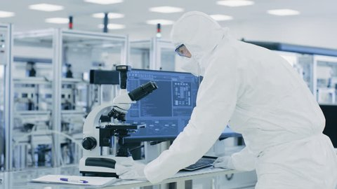 In Laboratory Scientist in Protective Clothes Doing Research Uses Microscope and Personal Computer. Modern Manufactory Producing Semiconductors and Pharmaceutical Items.