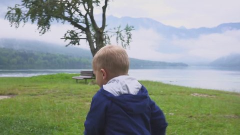 the little boy walks near the mountain lake. Running and frolicking in nature.