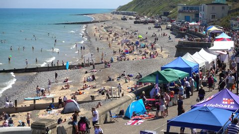 NORFOLK, ENGLAND, JULY 22ND, 2018: During a long UK heatwave, people paddle in the calm sea, relax on the busy beach, and walk along the promenade at Cromer, on the north Norfolk coast in England, UK.