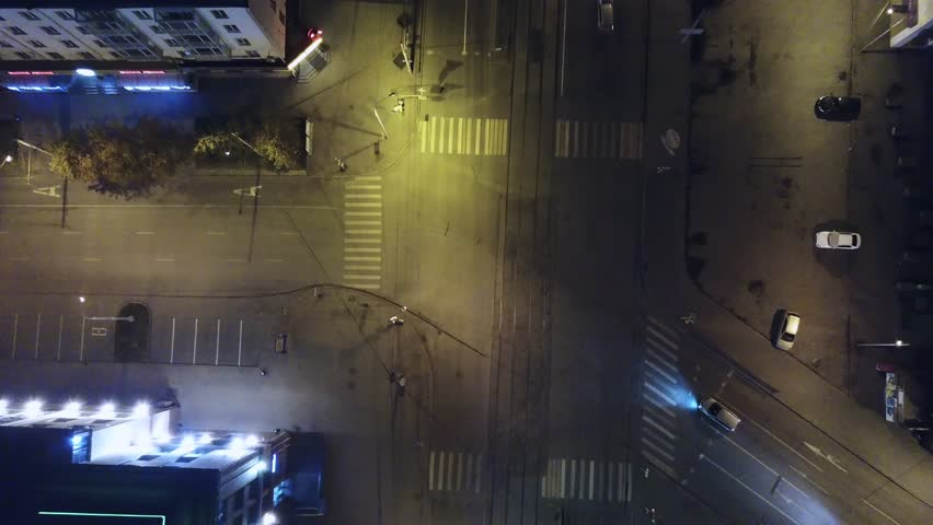 An aerial shot of cars driving through small downtown city with the lights and intersections late at night. Clip. Aerial view of highway empty road city street in night