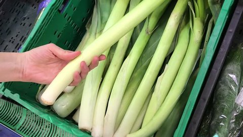 A woman's hand choosing and buying a lot of leek at a supermarket. Closeup shot.