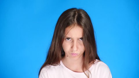 Close up. good looking sullen girl pouts lips, on blue background. Offended teen girl