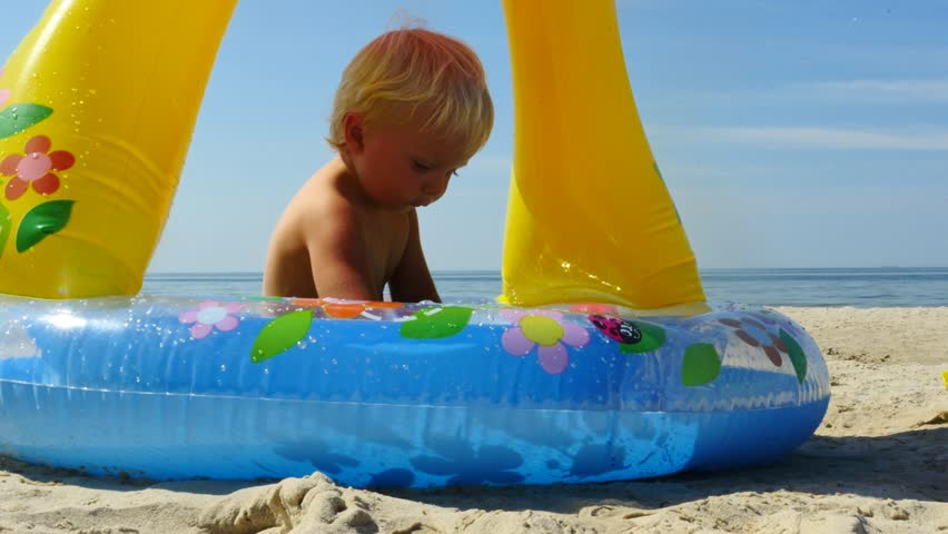 18 months old cute baby boy on the beach with shady defence