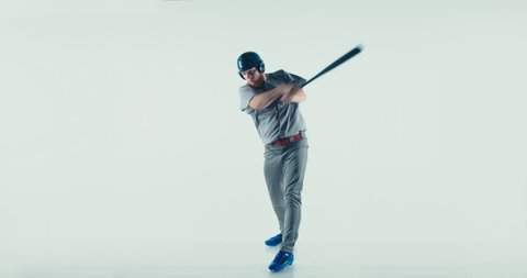 Caucasian professional baseball player batter wearing generic uniform hitting a ball isolated on white background. 4K UHD 60 FPS SLOW MOTION
