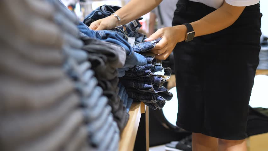 Woman Shopping For Jeans In Clothing Store.