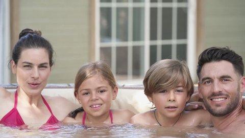 Family of 4 enjoying bath in spa hot tub