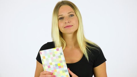 A young beautiful woman holds a book and smiles at the camera - white screen studio