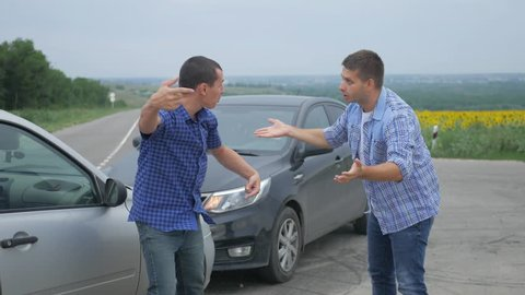 Two drivers argue about blame for accident by the side of damaged. Two male drivers argue over who is to blame for traffic accident. The concept of traffic.