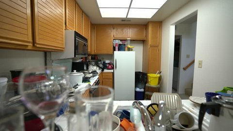 Dolly across messy condo kitchen with dirty dishes and clutter.