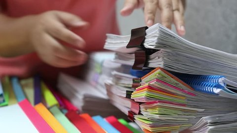 Asian teacher hands is searching for student's homework assignments archive with colorful papers on table to make a check and inspect. Stack of paperwork and reports. Education and business concept.