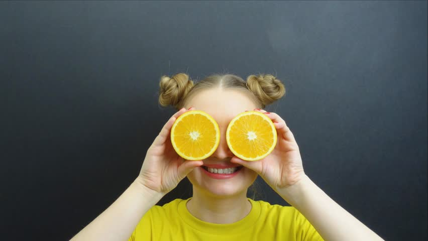 Portrait of beautiful girl with fruits on eyes stop motion loop.