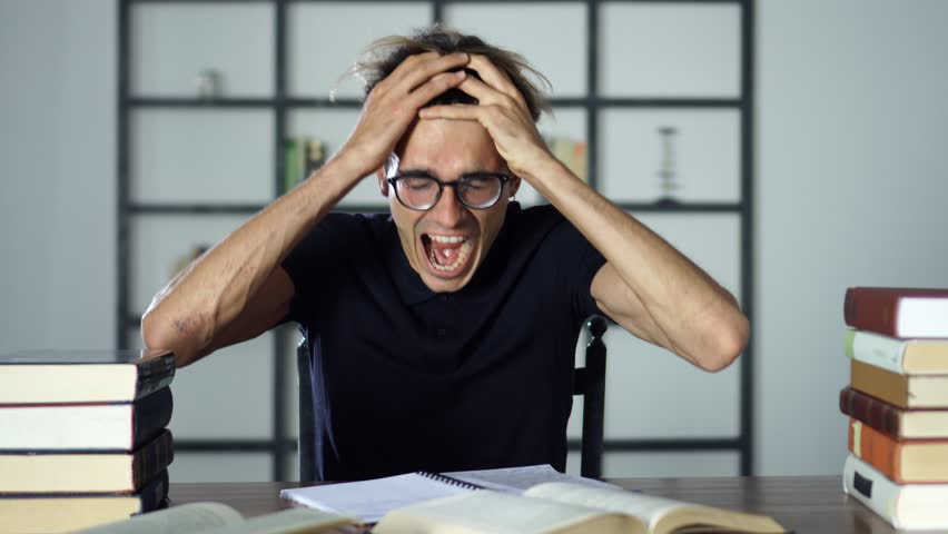 Stressed angry student screaming with open mouth while studying, reading books, cannot find any information from the textbook. | Shutterstock HD Video #1014621800