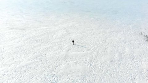 Aerial shot following lone man walking on snowy field in the middle of nowhere. Drone shot of ice tundra with stranded person lost in isolated cold environment. No hope of rescue in snowy disaster.