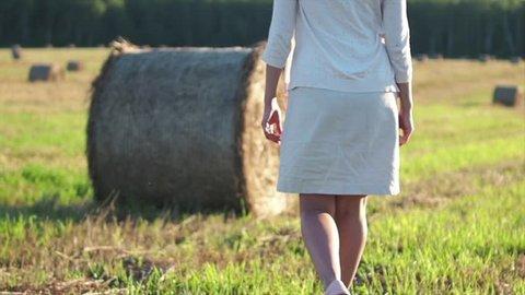 Cute girl in white dress is walking near haystack in field, slow motion video