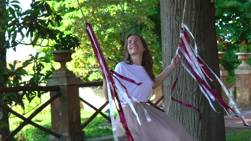 A beautiful girl swinging on a swing in the yard at a slow motion