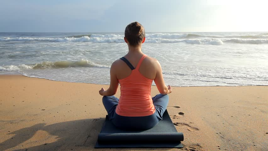 Woman doing yoga - meditate and relax in Padmasana Lotus asana pose with chin mudra outdoors at tropical beach on sunset | Shutterstock HD Video #1014692630