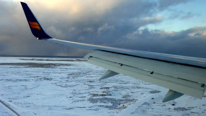 REYKJAVIK, ICELAND, JANUARY 2018: Stable POV passenger shot view looking at snowy landscape during winter from above in sky during landing with the airplane wing in sight and touching the ground #1014694550