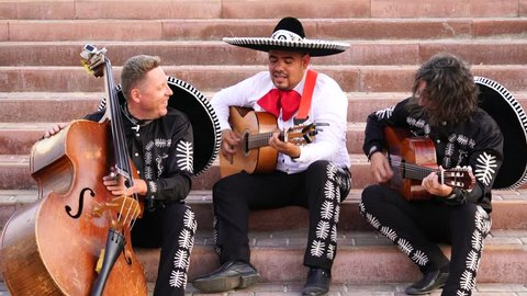 A trio of mexican musicians mariachi are sitting on the stairs in the street and playing music