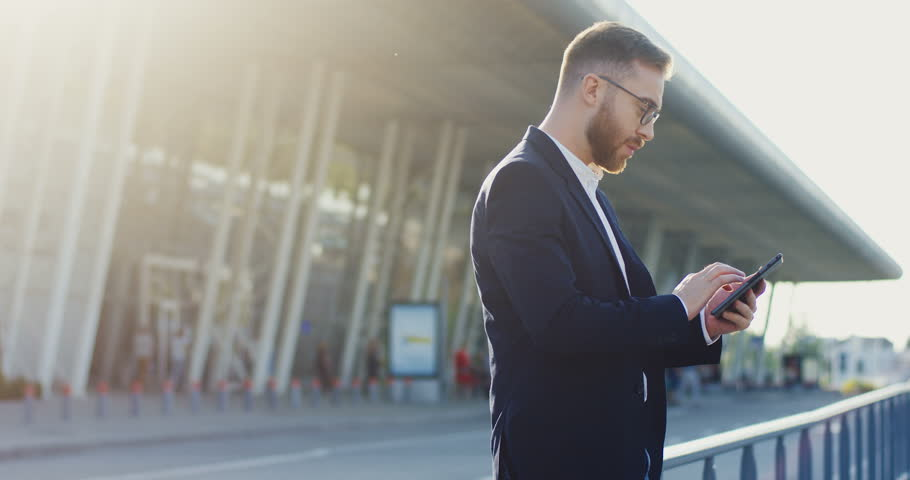 Good looking stylish male office worker using his smartphone, taping and scrolling, then turning head to the camera and back. At the airport or other big glass building. Side view. | Shutterstock HD Video #1014757790