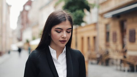 Young businesswoman using mobile phone near business center. Woman using mobile phone for business communication voice message. Concept: new business, communication, banker, call, voice translator