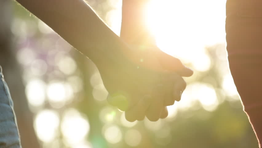 Hands held together with sunlight flare shining in the background #1014802700
