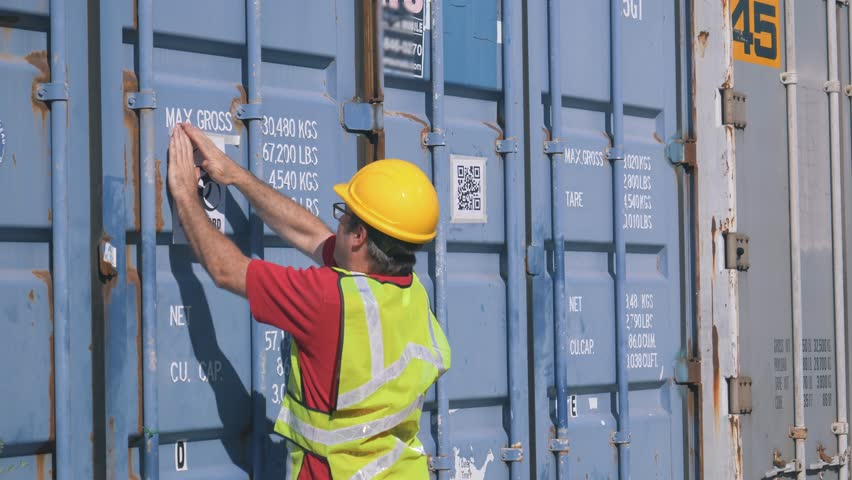 Shipping worker sticking a biohazard sign on a shipping container in a shipping yard filled with large shipping containers.