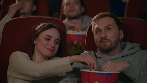 Young people watching movie at cinema theatre. Friends couple eating popcorn in slow motion