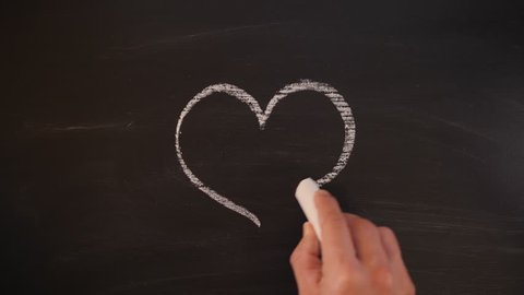 Man Drawing Romantic Heart on Chalkboard. 4K Valentines Day or Wedding Design Background Concept.