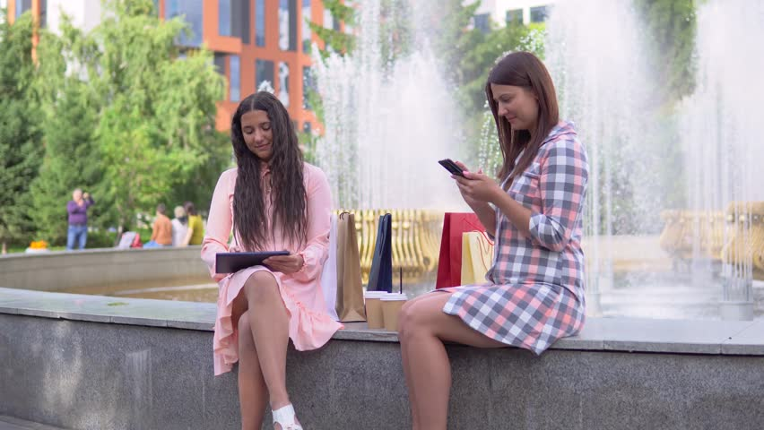 Two attractive girls after shopping are sitting in a park near the fountain in sunny weather using a phone and a tablet having a good mood. 4K | Shutterstock HD Video #1014852880