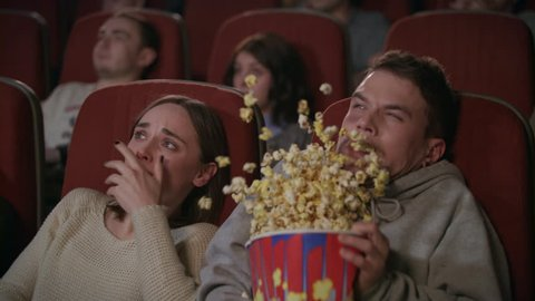 Young couple watching horror film in movie theatre. Guy sprinkle popcorn on girl in movie theater. Scared guy jumping in seat and spilling popcorn in slow motion. Shocked people watching horror movie