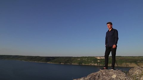 Young attractive man standing othe lands edge and looking far away. Sunny summer time.