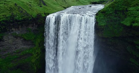 Aerial view close up of giant waterfall in Iceland filmed in slow motion
