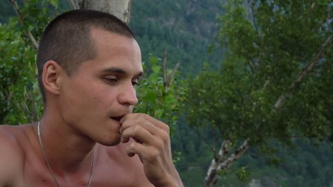 Pensive young man eating sunflower seeds in nature. Close up.