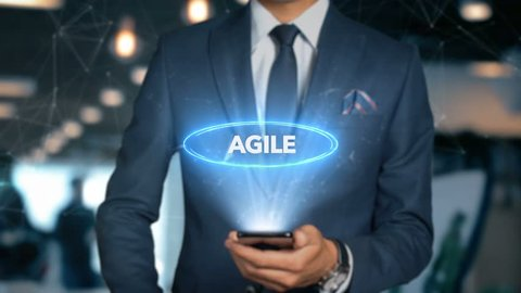 Businessman With Mobile Phone Opens Hologram HUD Interface and Touches Word - AGILE
