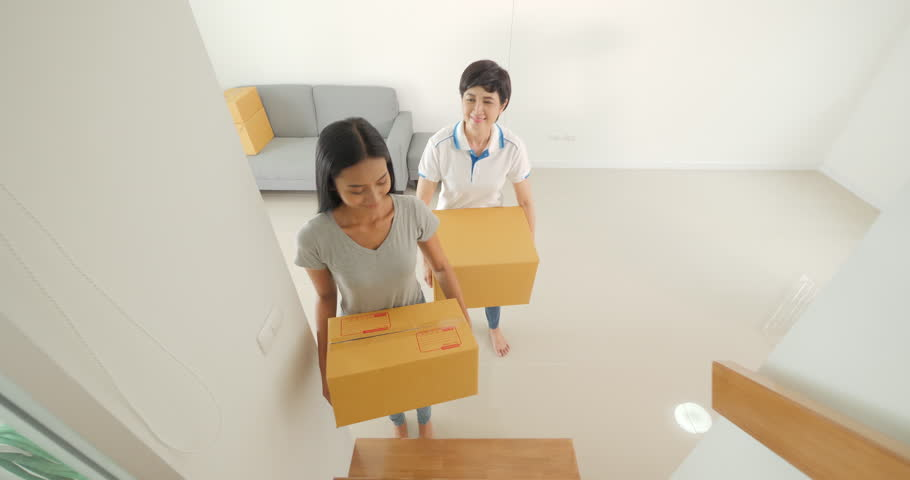 Happy asian women LGBT lesbian couple holding boxes entering new modern house.