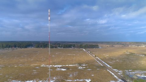The tall GSM 4G 5G glas micro fibre communications tower on the middle of the field with the small snow on the ground