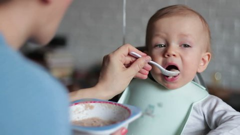 Mother feeding her baby son with porridge, close up