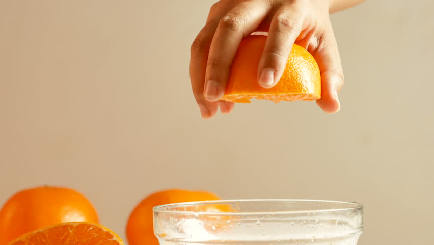 Women are using their hands to squeeze half orange to make the orange juice into the glass bowl