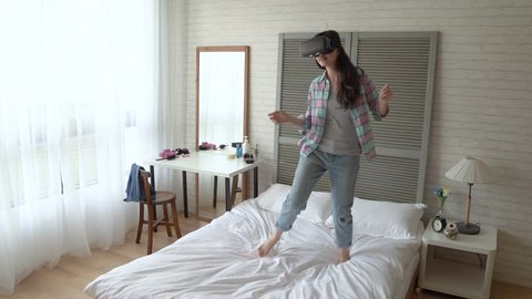 Asian woman sinks herself in the video game. She image she is the superstar in the VR goggle screen. She dances in high mood and enjoys the game.