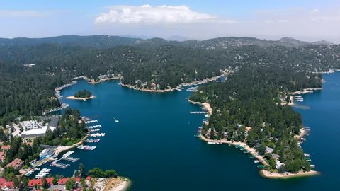 Aerial Shot Descending Over Lake Arrowhead with Water, Trees, Boats, and Lake Arrowhead Village all in View