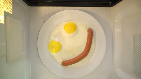 Making microwave breakfast meal. Smiling face of fried eggs and sausage on white plate microwaving top view.