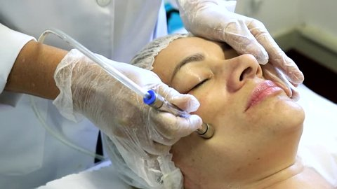 The cosmetologist does the procedure Microdermabrasion of the facial skin of a real woman